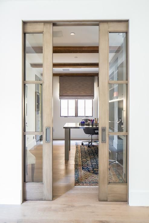 Wood And Gl Pocket Doors Open To A Work E Furnished With Gray T Shaped Desk Placed Above Red Blue Persisan Runner
