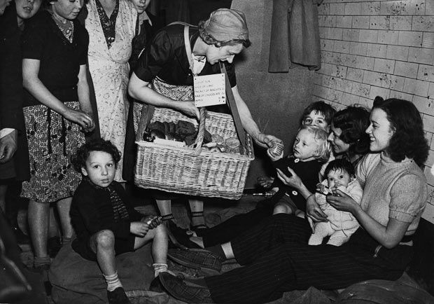 1940: A woman selling biscuits to people using an underground tube station as an air raid shelter.