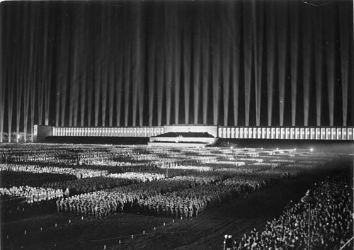 Albert Speer's created the Cathedral of Light - a main aesthetic feature of the Nuremberg Rallies - that consisted of 130 anti-aircraft searchlights at intervals of forty feet, aimed skyward to create a series of vertical bars surrounding the audience - a brilliant effect, both from within the design and on the outside. Adolf Hitler commissioned Speer to design and organize the Nuremberg Parade Grounds for the annual celebrations. It is still considered amongst Speer's most important works.