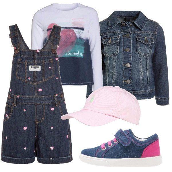 Salopette di jeans, maglietta bianca a maniche lunghe con stampa, giacca di jeans. Scarpina blu e rosa con chiusura in velcro e cappellino rosa con visiera.