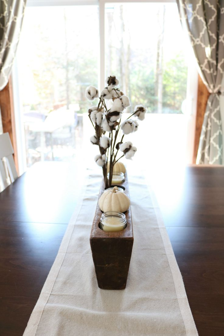 A simple, neutral centerpiece of preserved cotton, white pumpkins, and candles in an antique sugar mold