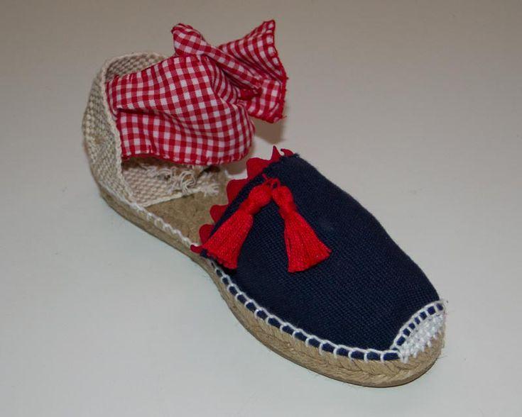 Alpargata de esparto plana azul marino, atada al tobillo con cuadro vichy rojo y detalle de borlas en rojo. Precio de venta: 20,00 €