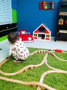 "I love the idea of fake grass in a kid's play space! If you can't get the kids outside, get the ""outside"" in! Might help 'em love it more! ------ train track rug, car wall art, car cushion and road mural - love this room"