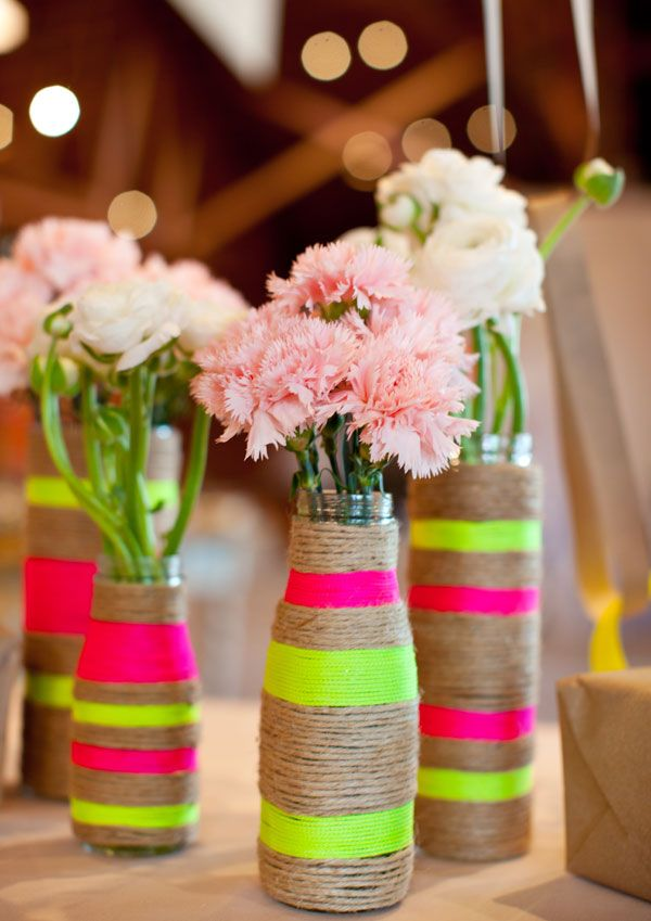 by Birds of a Feather Photography  For a more rustic and opulent look, wrap twine around the bottles. Add a little bit of color too. These neon shades of yellow and pink really make the vases pop and the delicate pastel flowers complement them beautifully.