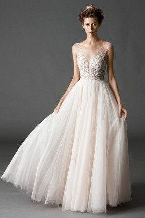 Dreamy, ballerina inspired A-line gown, featuring an Illusion yoke with a plunging neckline, delicate beading and Swarovski Crystals on the bodice, pearl buttons down the back, and a full Soft Net ski