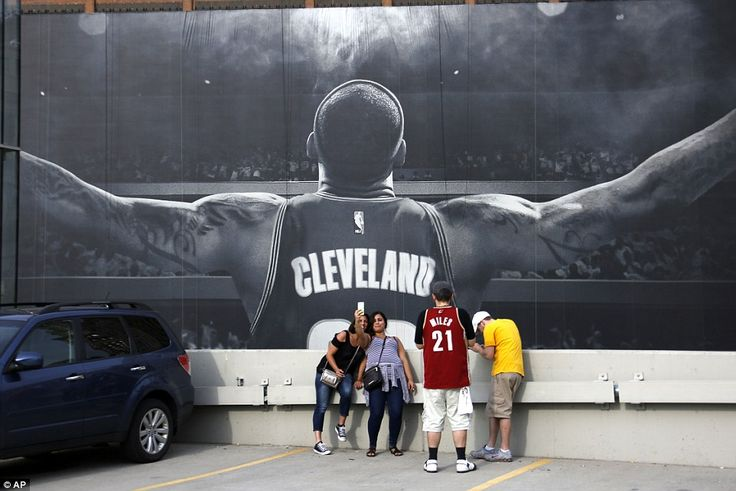 Cleveland Cavaliers fans take a selfie in front of a mural of star player James - he led his side to a historic first NBA title triumph