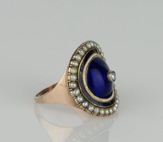 Este encantador anillo de esmalte georgiano está elaborado en oro de quilates rosa 9. Cuenta con un centro perla conjunto de bisel con un envolvente de guilloche azul acentuado con una franja de esmalte blanco y azul. El borde externo del anillo es acentuado con perlas media 2 mm.  Peso: 7,8 gramos Medidas: 23 x 21,5 mm - cara Tamaño: 9.25 Notas de la condición: restauraciones en esmalte blanco, esmalte azul delgada frontera tiene chips, pérdidas y daños, posiblemente de tamaño al mismo…