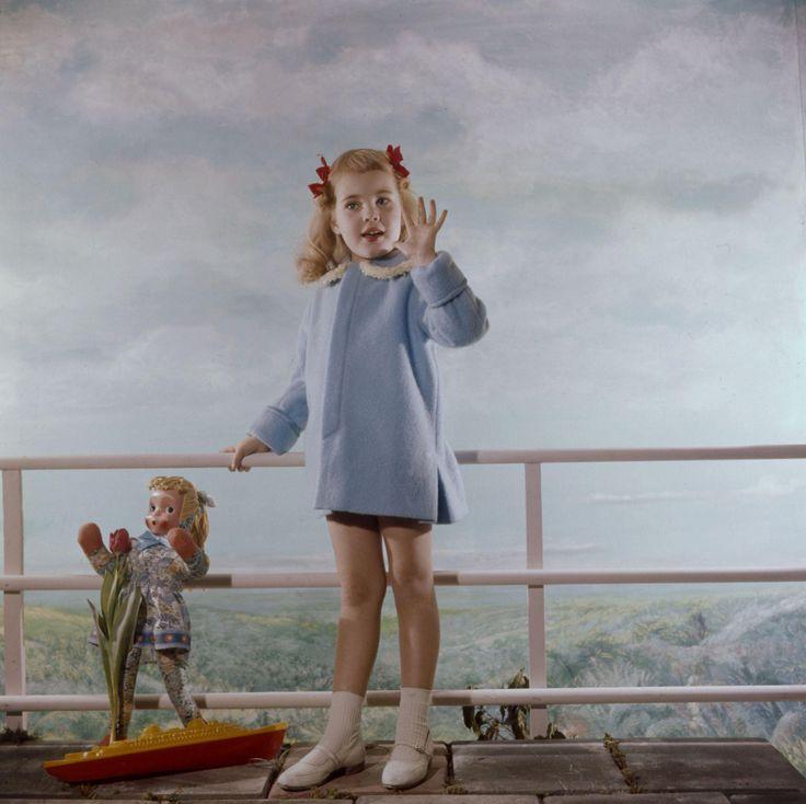 Kindermode, atelierfotografie. Meisje met staartjes in het haar, in lichtblauw jasje (manteltje) en witte schoenen en sokjes. Studio-opname met speelgoed in uitkijkpunt-decor met stoeptegels en balustrade tegen achtergrond van door fotograaf geschilderd landschap. Nederland, 1960-1965.