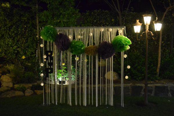 Photocall diseñado por Dimeic: cortina de hilos con guirnalda de pompones, guirnalda de luces e iniciales de pizarra