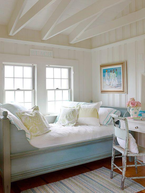 Cottage bedroom: blue bed, white paneled walls