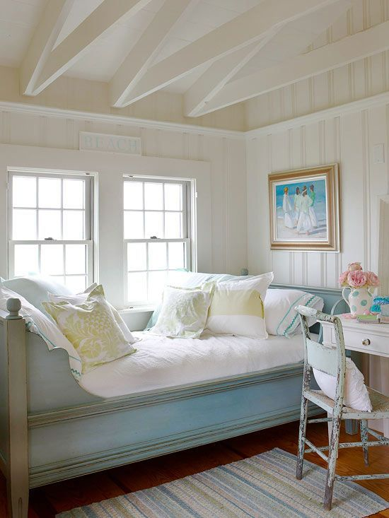 White beamed ceiling and paneled walls. Antique bed.