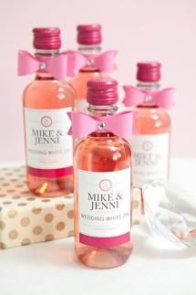 A set of small wine bottles with custom labels and pink bows. - Something Turquoise