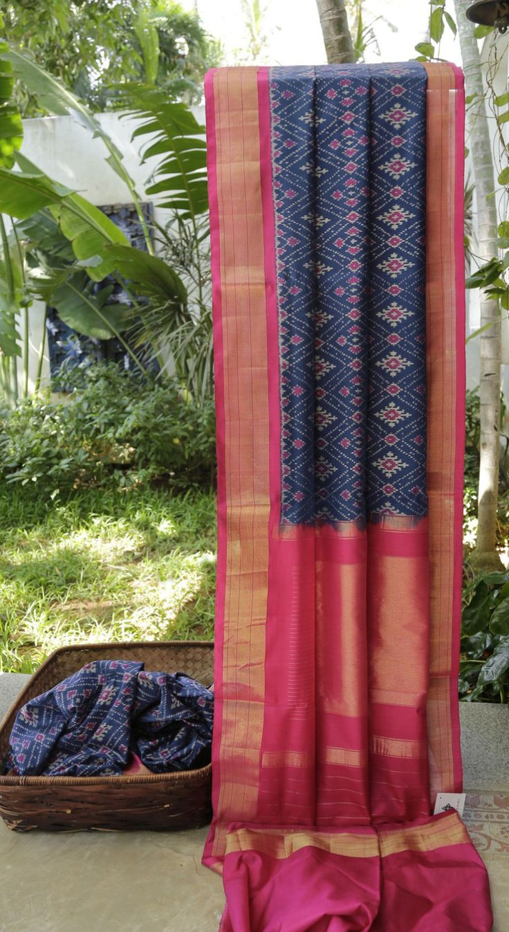 This navy blue silk sari has typical Ikat pattern in cotton white and magenta thread work. The contrasting border and pallu are in magenta and gold zari giving it a rich look for ocassions