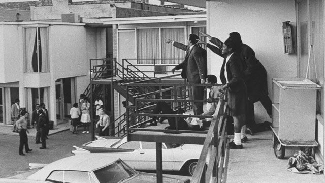Civil rights leader Andrew Young, left, and others on the balcony of the Lorraine Motel point in the direction where gunshots came from after the assassination of civil rights leader Martin Luther King Jr. on April 4, 1968. His body lays at their feet.