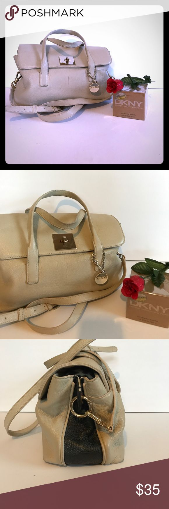 DKNY Handbag Cute cream/black Handbag by DKNY. Gold-toned hardware is stamped with DKNY authentication, signature lining and removable /adjustable shoulder strap. There are three large inside compartments. two have magnetic closures and the center is zippered. Two open pockets inside and one small zippered pocket. On the back of the bag there is a open pocket. There is a pen mark on the front of bag/slight wear on the edges of handles, price reflects. Can be used year round, color very…