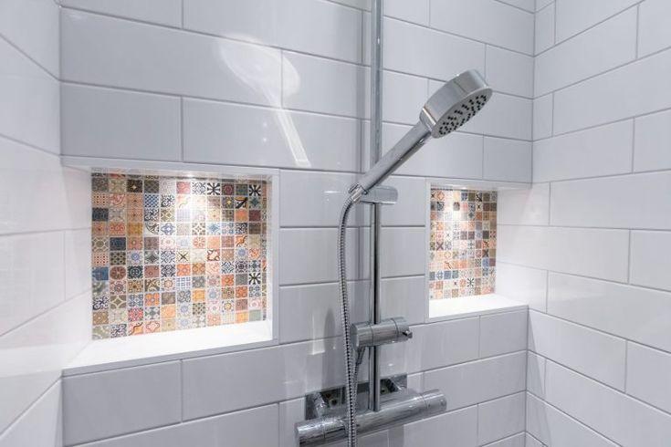 Ljust och fräscht badrum med vacker mosaik. Det vita liggande kaklet bryts av med mönstrad mosaik runt spegeln och i duschens upplysta nischer. Duschutrymmet utgörs av en helkaklad vägg och är utrustad med både handdusch och takdusch. Handfatet är vägghängt med en underdel i svart trä.