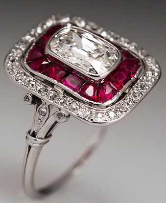 This magnificent Art Deco ring features a stunning natural 1.36 carat antique cushion cut diamond center stone surrounded by a halo of lab created ruby accents and a second halo of natural diamonds. The ring features a wonderful low profile design and the craftsmanship that went into it nearly 100 years ago is superb.