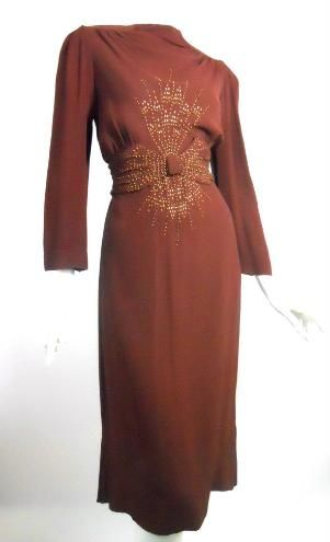 1940s cinnamon crepe dress with bevel head and round brassy metal studs. Cinches in back, back metal zipper. Shirred at shoulders. Via Dorothea's Closet Vintage.