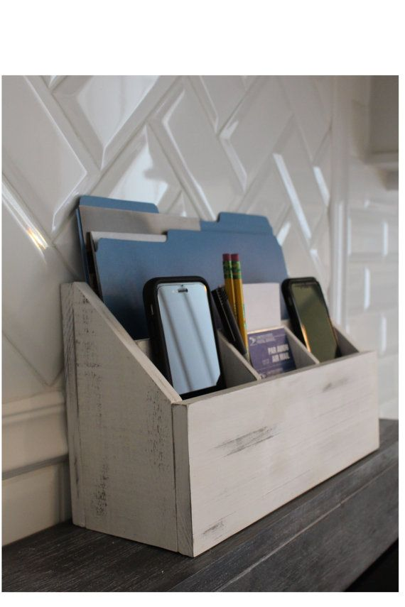 Keep your phones and iPad or tablet charged while hiding your paper and mail clutter. This stylish rustic wood stand can be used on your countertop, desk, or nightstand to organize your belongings. The organizer has 3 compartments in the front, 2 of which are raised to allow the chargers room underneath without bending the cords, which then can go through the drilled holes in the back of the station. The large back compartment can hold folders, an iPad, or tablet. Extra propping blocks are…