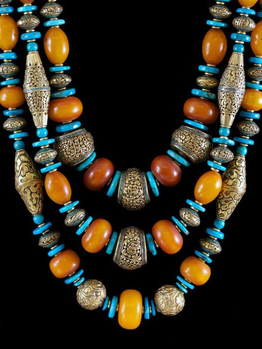 "African amber, Nepalese brass, and turquoise. The ""amber"" beads appear to be imitation made form phenolic and/or resin."