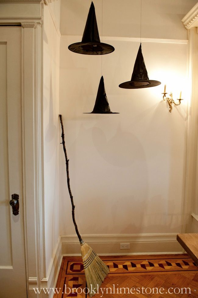 Suspend witch hats from the ceiling and prop a rustic broom against the wall for a simple yet eerie entryway look.