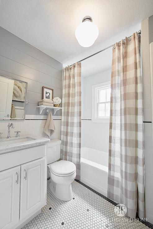 Cabin boy's bathroom features upper walls clad in gray shiplap and lower walls clad in white subway tiles accented with black pencil tiles lined with a white washstand topped with white marble under a rectangular pivot mirror. A white wall shelf with brackets stands over the toilet next to a drop-in shower finished with two tan buffalo check shower curtains.