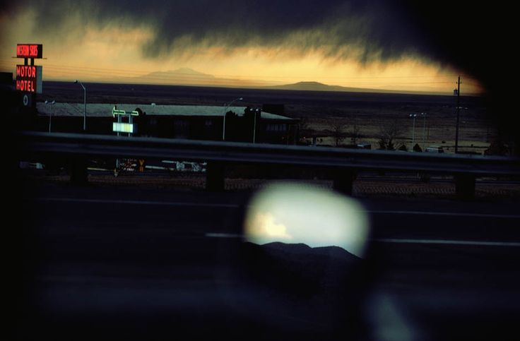Ernst Haas. A view from a moving car as it passes the Western Skies Motel in stormy weather, Colorado, USA, March 1977. Mountains can be seen reflected in the wing mirror.