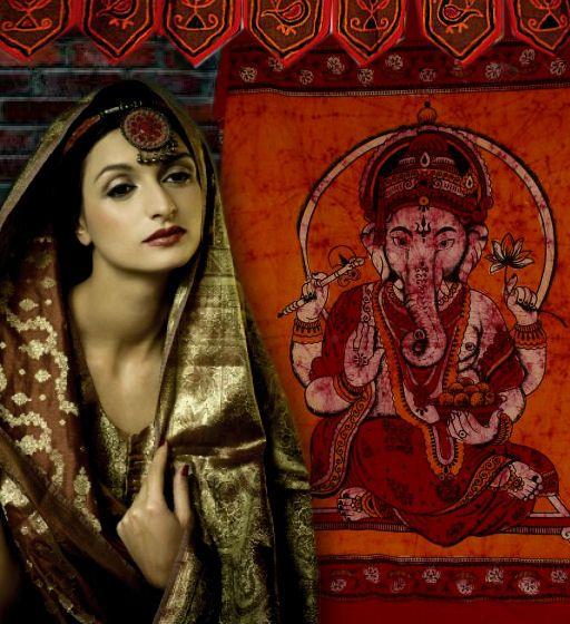 Indiase schoonheid met groot wanddoek van Ganesha in de achtergrond