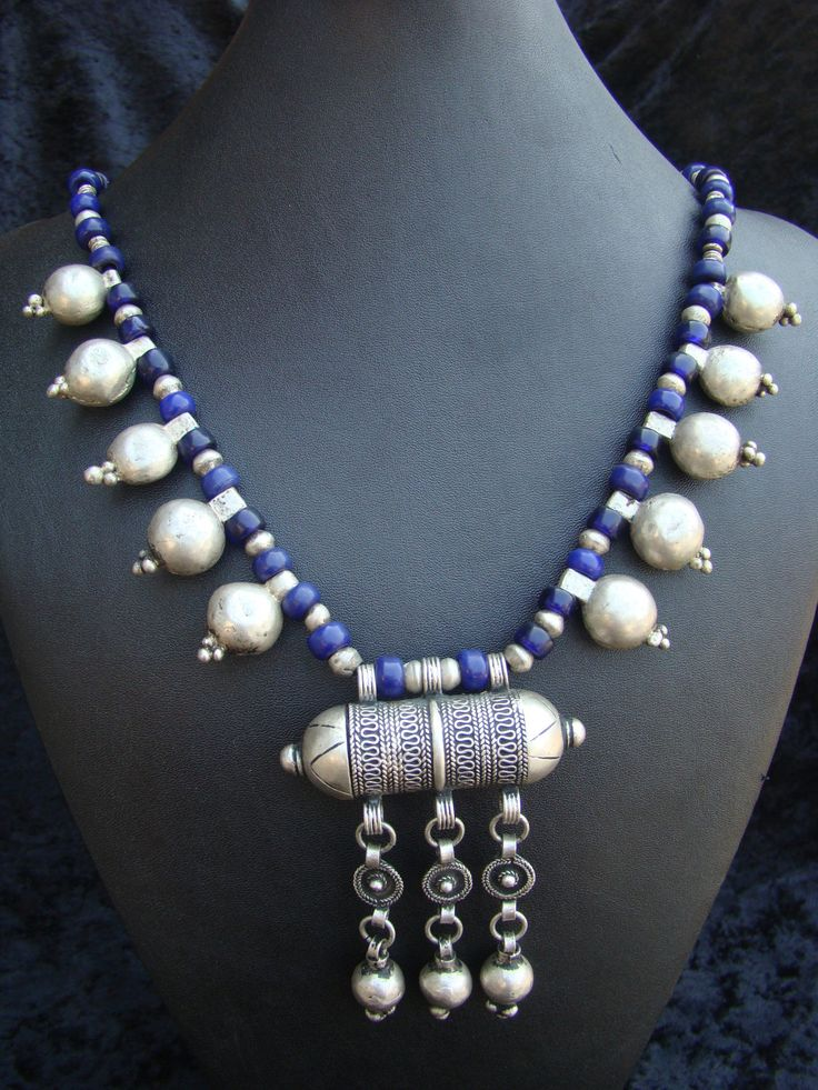 by Nancy Sathre-Vogel | The focal point of this necklace is a vintage cylindrical prayer box from Ethiopia.  This has been combined with old silver Ethiopian fertility beads and blue glass beads | The Ethiopian silver pieces in this necklace are likely to contain between 60 & 85% silver.  {150$}