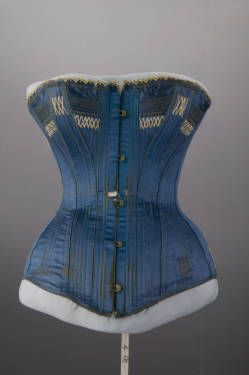 Basic ID Wedding corset, 1884. Embroidered silk satin, lace. Maker unknown. Gift of Mrs. Noreen Corcoran. X.3491.2010  Title Corset  Date 1884  Description Corset of blue silk satin. Yellow silk thread embroidery under breast and along hem. Center front corset closure; center back metal grommets with cotton laces. Linen twill lining.