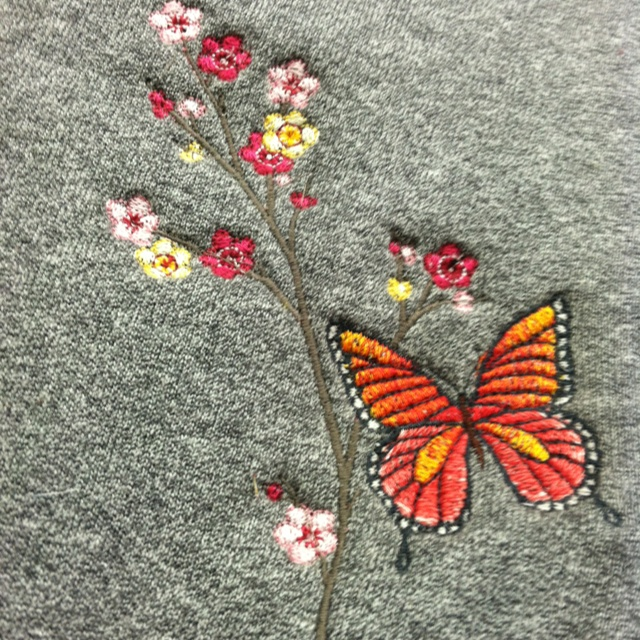 Butterflies embroidered on a sweatshirt.