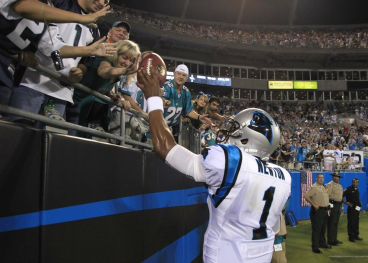 Carolina Panthers' Cam Newton (1) hands a football to a fan after a Panthers touchdown against the Miami Dolphins during the first quarter of a preseason NFL football game in Charlotte, N.C., Friday, Aug. 17, 2012. (AP Photo/Chuck Burton) AP2012