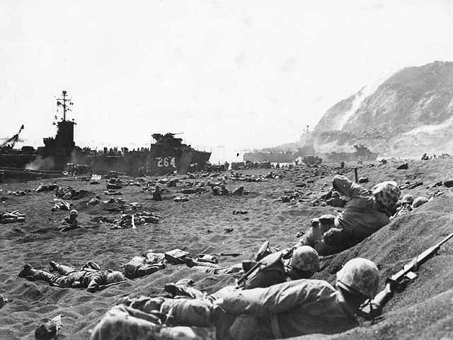 Marines burrow in the volcanic sand on the beach of Iwo Jima. This Day in WWII History: Feb 19, 1945: Marines invade Iwo Jima