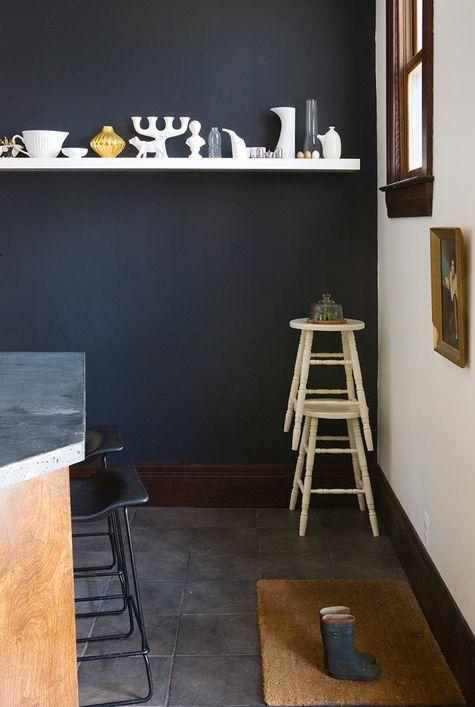 De witte accessoires op de witte plank worden nog frisser tegen de donkere muur.