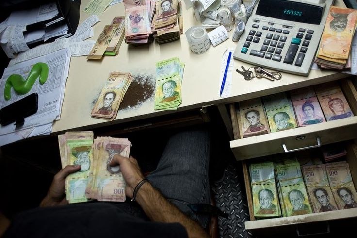 At a delicatessen counter in eastern Caracas, Humberto Gonzalez removes slices of salty white cheese from his scale and replaces them with a stack of bolivar notes handed over by his customer. The currency is so devalued and each purchase requires so many bills that instead of counting, he weighs them.