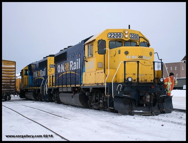 Extra 313 Conductor Sheldon  is captured communicating with his Engineman Shawn as they head towards the yard to pick up Kapuskasing bound empties at Cochrane utilizing GP40-2's 2202 and 2200 February 17th.