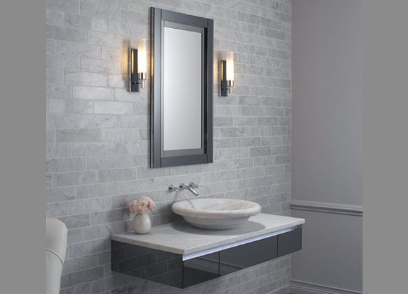 This contemporary bathroom features a vanity and floating sink the gray brick walls are adorned with light sconces a white armchair accents the space
