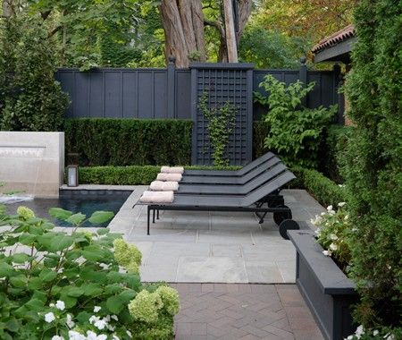.Refined Backyard Design A poolside stone terrace complements neat landscaping. Hits of black are integrated into this outdoor space's neutral palette, seen in the fencing, trellis and streamlined chaises