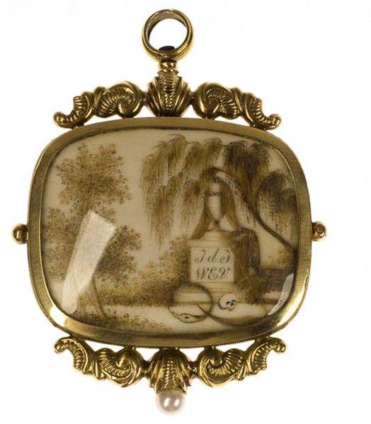 14krt geelgouden Biedermeier horlogesleutel. Deze horlogesleutel, een rouwsieraad, is versierd met haarwerk. Aan de voorzijde is een urn te zien met een treurwilg, een schedel, een zeis en de slang die in  zijn eigen staart bijt. Op de achterkant zijn krullen te zien en twee vergeet me nietjes. 67 x 50mm  € 1.395,-