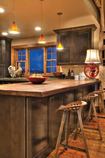 Reclaimed beams were milled into a wood-plank countertop. Tractor seats were found at a yard sale and new metal legs were created.