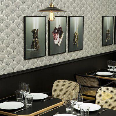 L'atmosphère intimiste des tables est apportée par le soubassement laqué en noir,  le papier peint japonisant et les touches de jaune sur les fauteuils en cannage.