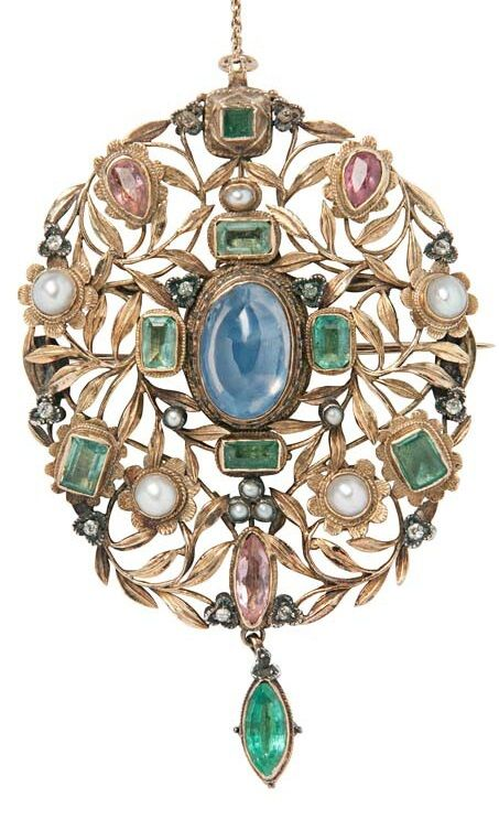 Arthur and Georgie Gaskin - An Arts and Crafts Gold Gem-set Pendant/Brooch, Circa 1909. Of floral and foliate motifs, bezel-set with foil-backed sapphires, pink gemstones, and a sapphire, with single-cut diamond and seed pearl accents, reverse with floral decoration, unsigned, 3 in. This piece is believed to be part of a larger necklace presented by the Lord Mayor of Birmingham to Queen Alexandra upon her visit to the city in 1909.