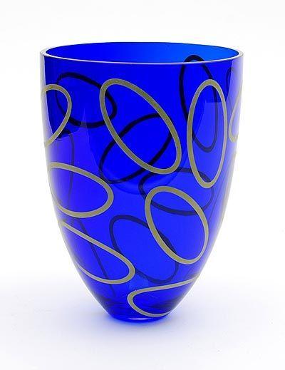 Olaf Stevens - serica vaas  Het ontwerp van deze blauwe serica glas vaas met ovalen is van Olaf Stevens. De vaas is genummerd 527/700 en gesigneerd door Olaf Stevens. De ovalen op de serica vaas zijn goud van kleur. Gemaakt bij Strömbergshyttan Sweden. De vaas is in goede conditie. Hoogte is 20.3cm diameter 15cm. De eerste unica van Olaf Stevens werd uitgevoerd door Royal Leerdam kristal waar hij van 1994 tot 1999 als ontwerper van industrieel glas was verbonden. Zijn ontwerpen zijn niet…