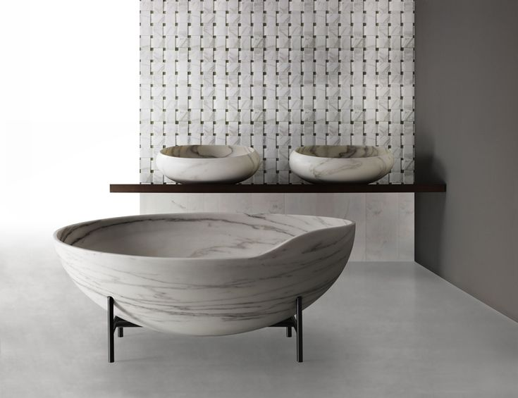 the suspended ellipsoidal marble bathtub expresses a form that is reminiscent of ancient tibetan bells.