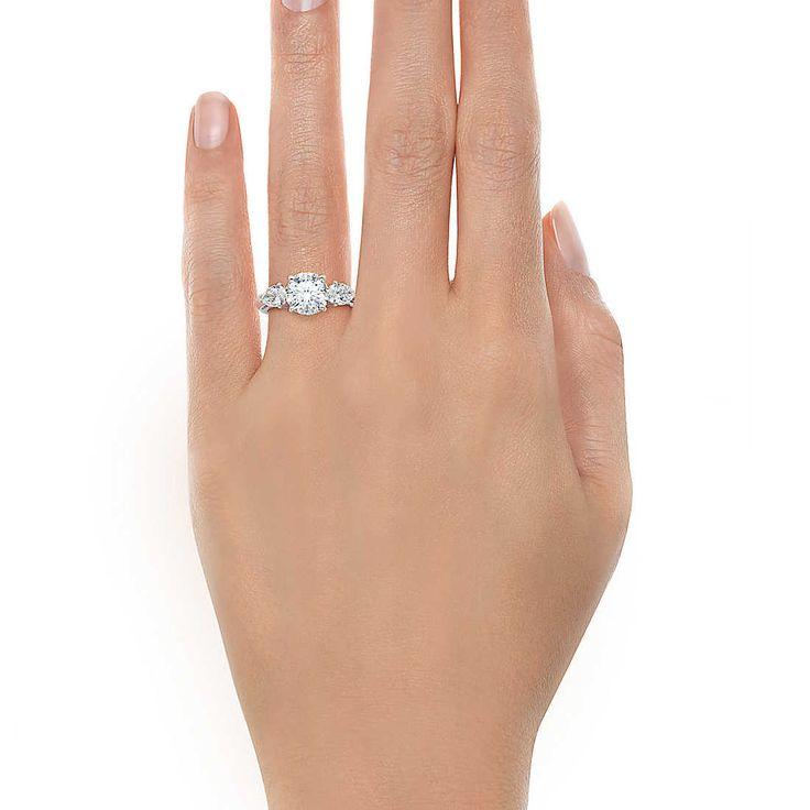 Dois diamantes Tiffany em forma de pera dão um ar de glamour a esta clássica pedra central de brilhante.