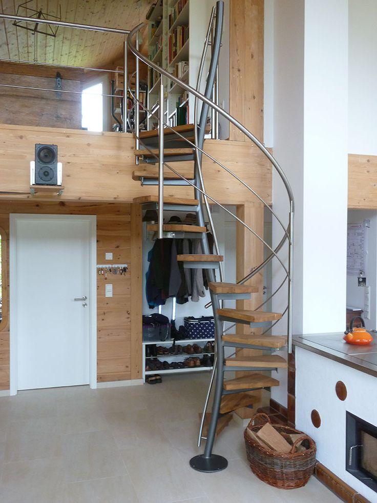 Raumspartreppe als frei im Raum stehende Designlösung zur Erschließung einer Galerie. Gewendelte Standsäule in lackierter Ausführung mit angeschweißten Stufenauslegern, aufgeschraubten Holzstufen und Edelstahltreppengeländer.