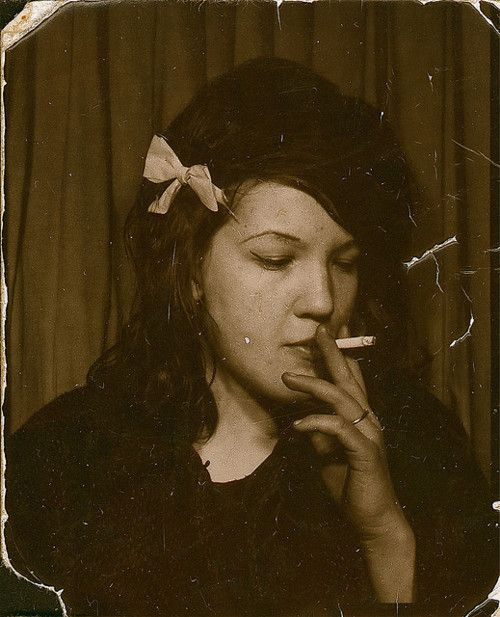 1964 Photo-booth picture. I think we can safely say that this girl is 'trouble'. Dark, badly applied makeup, backcombed hair that isn't well fashioned, and a cigarette. Love her!