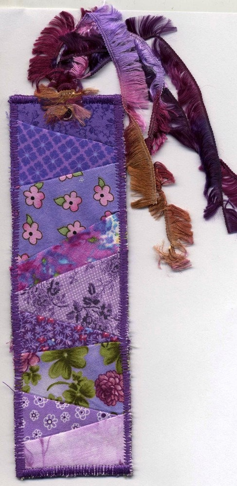 """This is a perfect bookmark to mark you page or to give as a gift. It's in a strippy quilt pattern and measures 2""""x7"""" with a tassel. It is made of Peltex and cotton fabrics. The back is covered in a gorgeous purple print fabric., $6.00"""