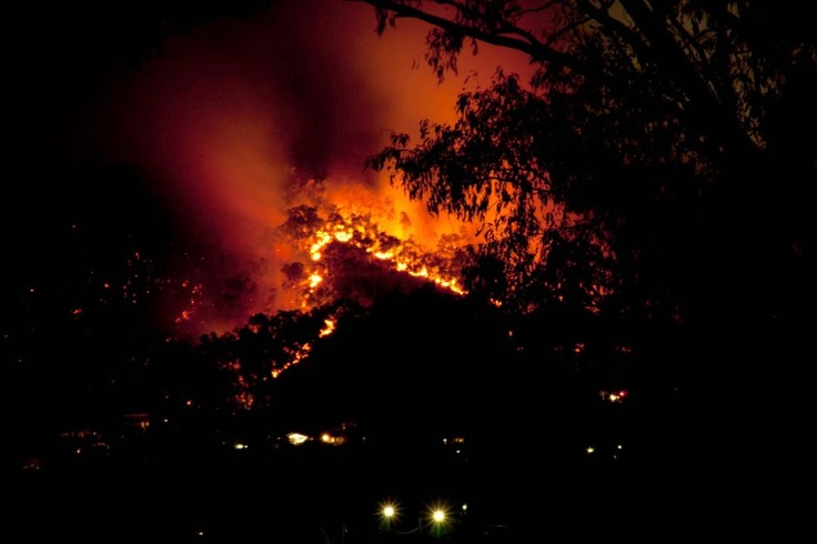 A bushfire burns behind the Gallipoli Barracks at Enoggera in Brisbane on the evening of August 19, 2012. The fire began after a controlled burn breached containment lines at the barracks earlier in the day, threatening homes in nearby suburbs.    Audience submitted: Sheila O'Boyle