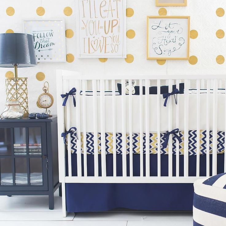 Beautiful nursery features mustard yellow polka dot walls lined with a white crib dressed in chevron bedding and a navy blue crib skirt flanked by a navy and white striped pouf near a dark navy nightstand topped with a gold arabesque lamp.